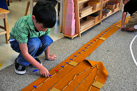 Children using bead chains to learn math at Montessori school