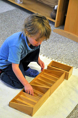 Montessori student using spindle boxes for math